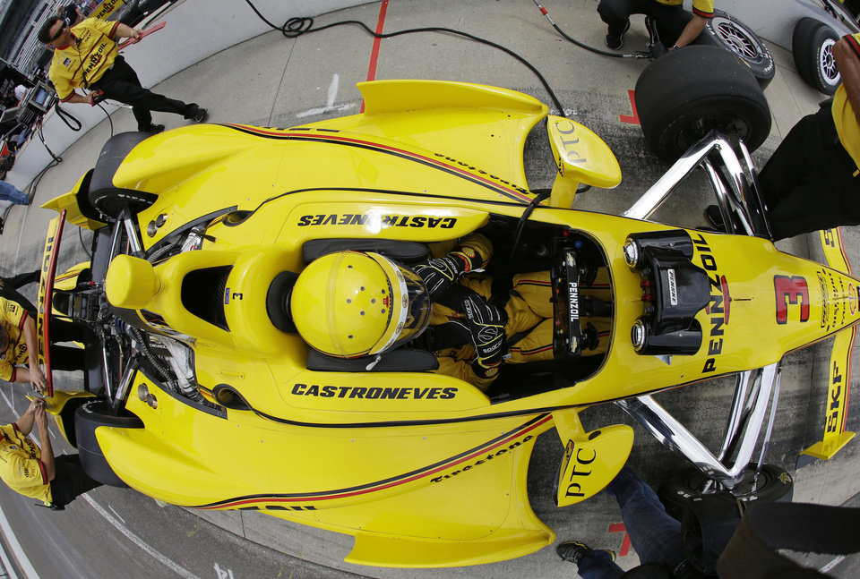 Photo - In this photo shot with a fisheye lens, Helio Castroneves, of Brazil, waits in his car during practice for Indianapolis 500 IndyCar auto race at the Indianapolis Motor Speedway in Indianapolis, Monday, May 12, 2014. (AP Photo)