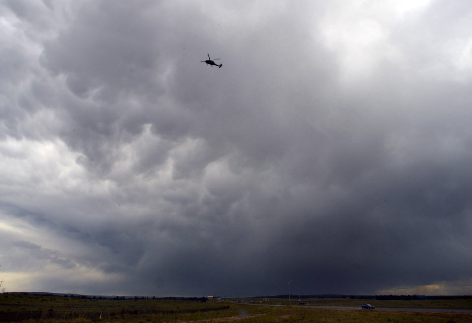 Photo - A helicopter flies underneath a thunderstorm that dumped rain on a trouble area of the Black Forest Fire near Colorado Springs, Colo. on Friday, June 13, 2013. Authorities lifted evacuations in a wide swath of terrain outside Colorado Springs on Friday as they said a surprise rain shower helped them expand containment of a wildfire that has destroyed 400 homes.  (AP Photo/Bryan Oller)