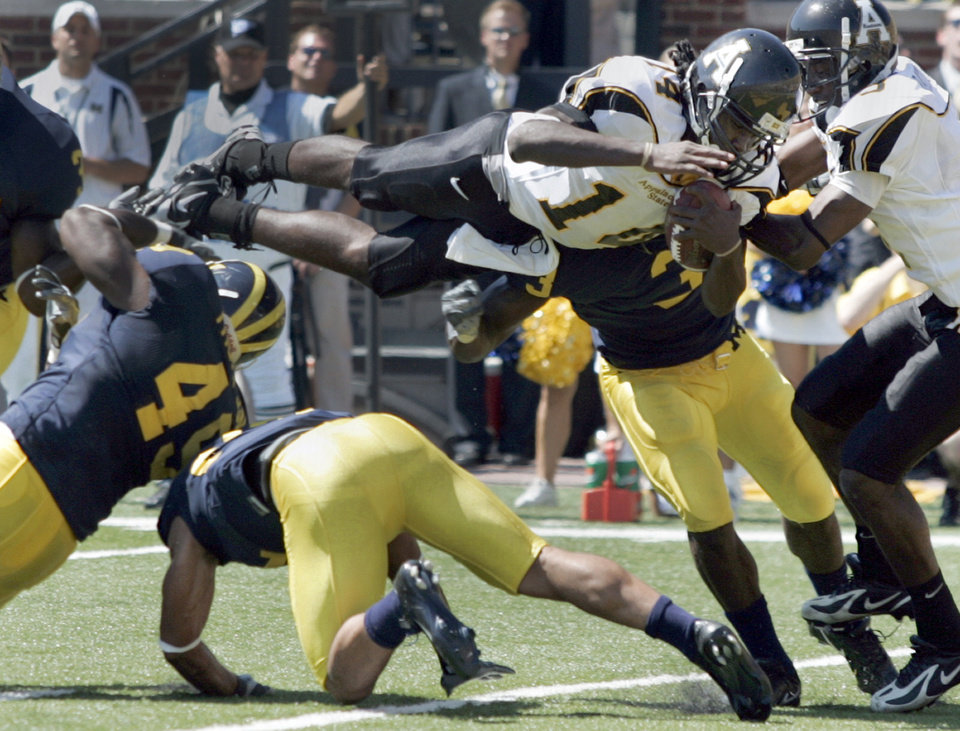 Photo - **FILE** In this Sept. 1, 2007 file photo, Appalachian State quarterback Armanti Edwards dives over Michigan linebacker John Thompson (49) and cornerback Brandon Harrison to score their fourth touchdown of the game during the second quarter of a college football game in Ann Arbor, Mich. Michigan is opening its 2014 season with Appalachian State this week, rekindling flashbacks to the day the Wolverines were on the wrong end of one of the biggest upsets in college football history.   (AP Photo/Duane Burleson, File)