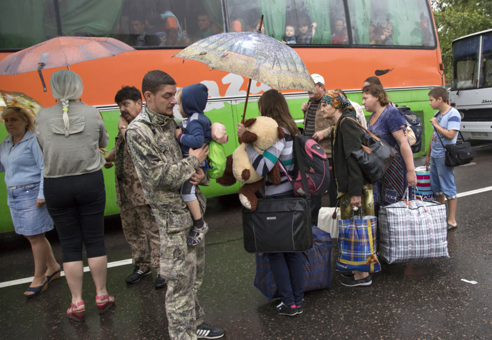 Photo - People board buses as they depart as refugees to Russia in the city of Donetsk, eastern Ukraine Monday, July 14, 2014. Five busloads of Internally Displaced People from the towns of Slavyansk, Karlovka, Maryinka and Donetsk left here Monday morning for the Rostov region in Russia to ask for refugee status there. (AP Photo/Dmitry Lovetsky)