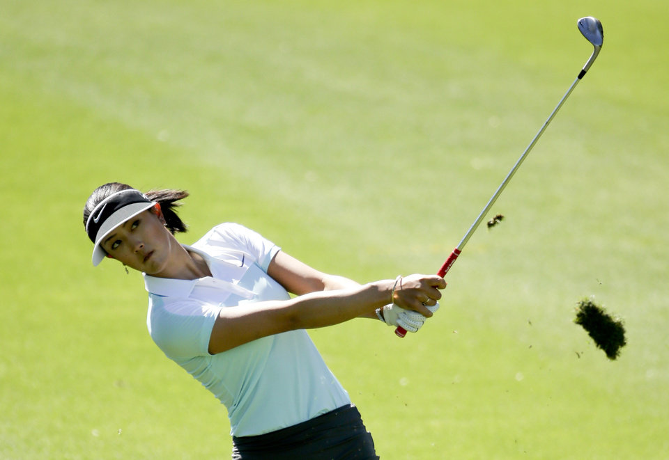 Photo - Michelle Wie hits from the fairway on the 15th hole during the first round at the Kraft Nabisco Championship golf tournament on Thursday, April 3, 2014, in Rancho Mirage, Calif. (AP Photo/Chris Carlson)