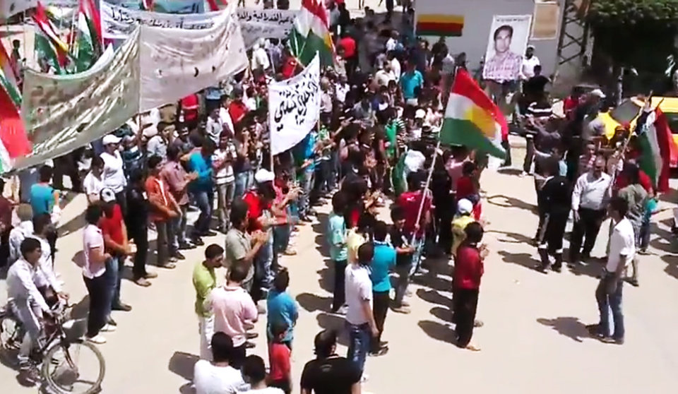 Photo -   This image made from amateur video released by the Shaam News Network and accessed Friday, May 4, 2012, purports to show Syrians chanting slogans and caring Kurdish flags during a demonstration in Qamishli, the capital of Syria's Kurdish heartland. (AP Photo/Shaam News Network via AP video) TV OUT, THE ASSOCIATED PRESS CANNOT INDEPENDENTLY VERIFY THE CONTENT, DATE, LOCATION OR AUTHENTICITY OF THIS MATERIAL