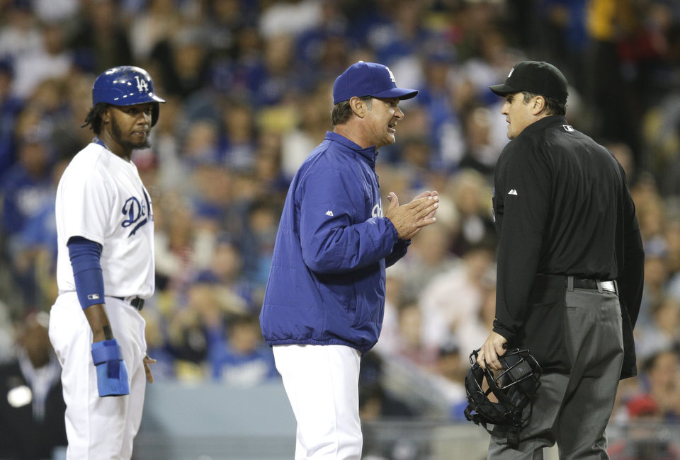 Photo - Los Angeles Dodgers manager Don Mattingly, center, argues with home plate umpire Mike DiMuro after Hanley Ramirez, left, was called out at home plate during the fifth inning of a baseball game against the Philadelphia Phillies on Thursday, April 24, 2014, in Los Angeles. (AP Photo/Jae C. Hong)