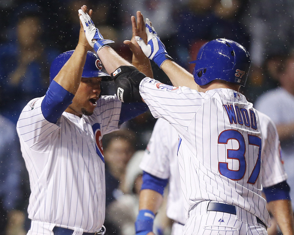 Photo - Chicago Cubs' Travis Wood, right, celebrates with Welington Castillo after Wood hit a three-run home run against the Arizona Diamondbacks during the second inning of a baseball game on Monday, April 21, 2014, in Chicago. Castillo scored on the home run. (AP Photo/Andrew A. Nelles)