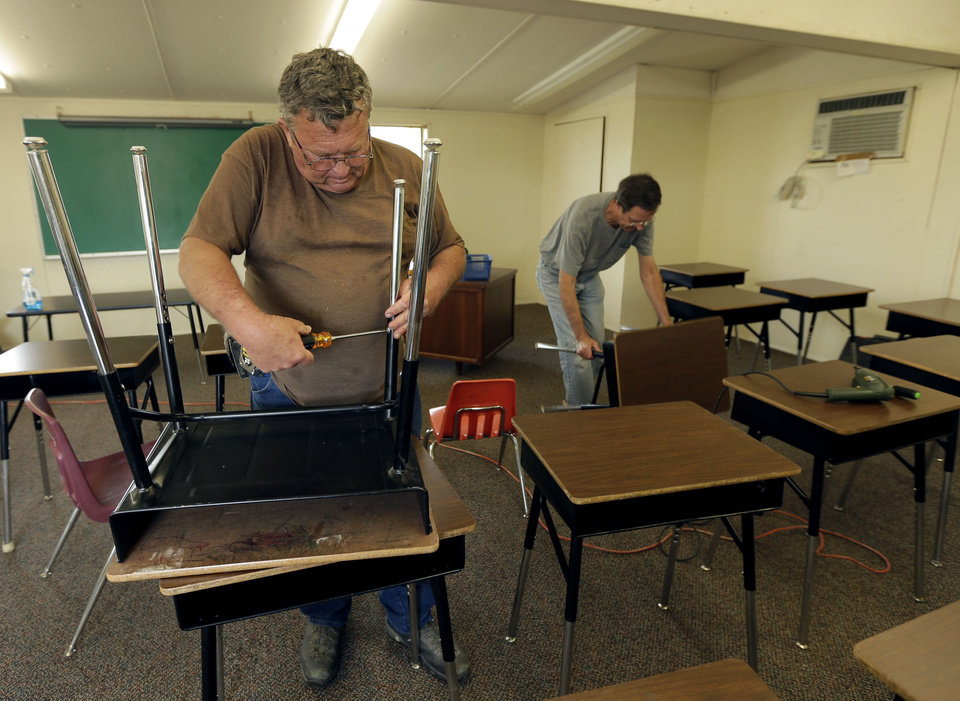 Photo - Volunteers Tommy Millender, left, and Brian Battershell, both from Temple, Texas arrange desks in a temporary classroom Sunday, April 21, 2013, four days after an explosion at a fertilizer plant in West, Texas. School will resume in for West students Monday in temporary facilities after Wednesday's explosion damaged three of the district's schools. The blast killed 14 people and injured more than 160 others. (AP Photo/Charlie Riedel)