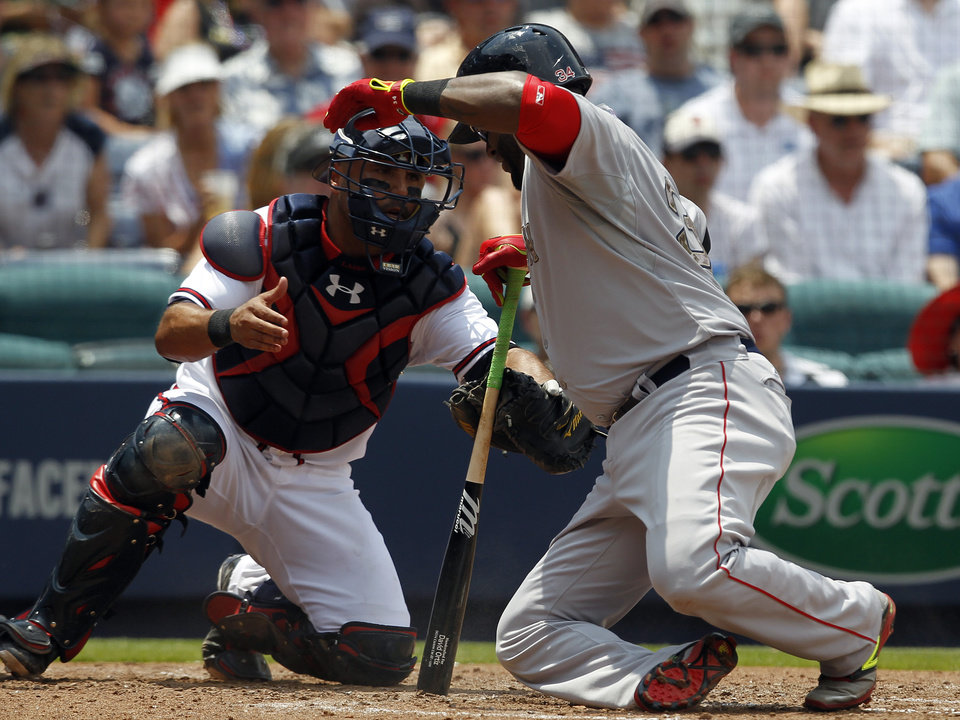 Photo - Boston Red Sox's David Ortiz (34) drops to the ground as Atlanta Braves catcher Gerald Laird reaches for him after fouling a ball into his leg during the fourth inning of a baseball game on Monday, May 26, 2014, in Atlanta, Ga. (AP Photo/Butch Dill)