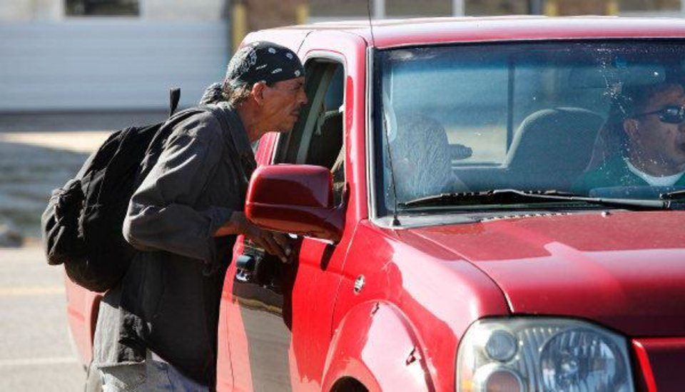 A homeless man leans into a truck window to hear about work possibilities. Men congregate in a parking lot to wait for people driving through looking to hire day laborers. Many downtown  homeless  stay in areas around downtown. <strong>JIM BECKEL - THE OKLAHOMAN</strong>