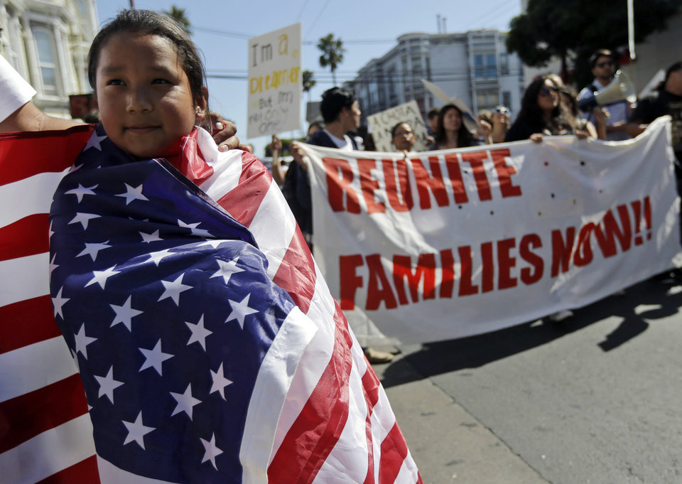 Photo - Maria Fernanda Medina, 7, wraps herself in a United States flag as she marches with her father, Jorge, during a May Day demonstration in San Francisco, Wednesday, May 1, 2013.  Demonstrators demanded an overhaul of immigration laws Wednesday in an annual, nationwide ritual that carried a special sense of urgency as Congress considers sweeping legislation that would bring many of the estimated 11 million people living in the U.S. illegally out of the shadows. (AP Photo/Marcio Jose Sanchez)