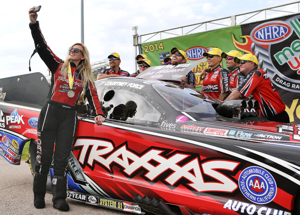 Photo - Funny Car driver Courtney Force takes a photo with her team after her championship run that gave her the 100th victory by a female driver in NHRA history at the NHRA Kansas Nationals drag races on Sunday, May 25, 2014, at Heartland Park in Topeka, Kan. (AP Photo/Topeka Capital-Journal, Chris Neal)