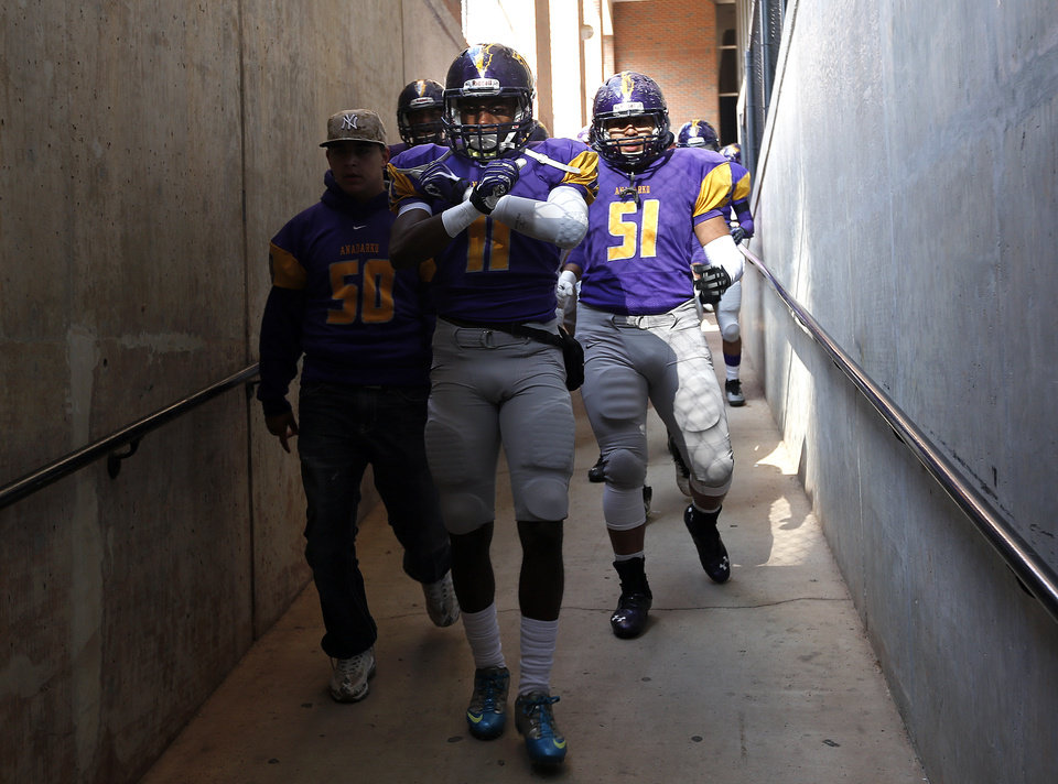 Photo - Anadarko's Mykel Shaw walks to the field before the Class 4A State Football Championship game between Anadarko and Poteau at Boone Pickens Stadium in Stillwater, Okla. Photo by Sarah Phipps, The Oklahoman