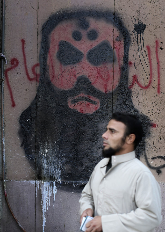 An Egyptian man walks past graffiti in Tahrir Square, Cairo, Egypt, Sunday, Dec. 9, 2012. Egypt's liberal opposition has called for more protests on Sunday after the president made concessions overnight that fell short of their demands to rescind a draft constitution going to a referendum on Dec. 15. (AP Photo/Hassan Ammar)