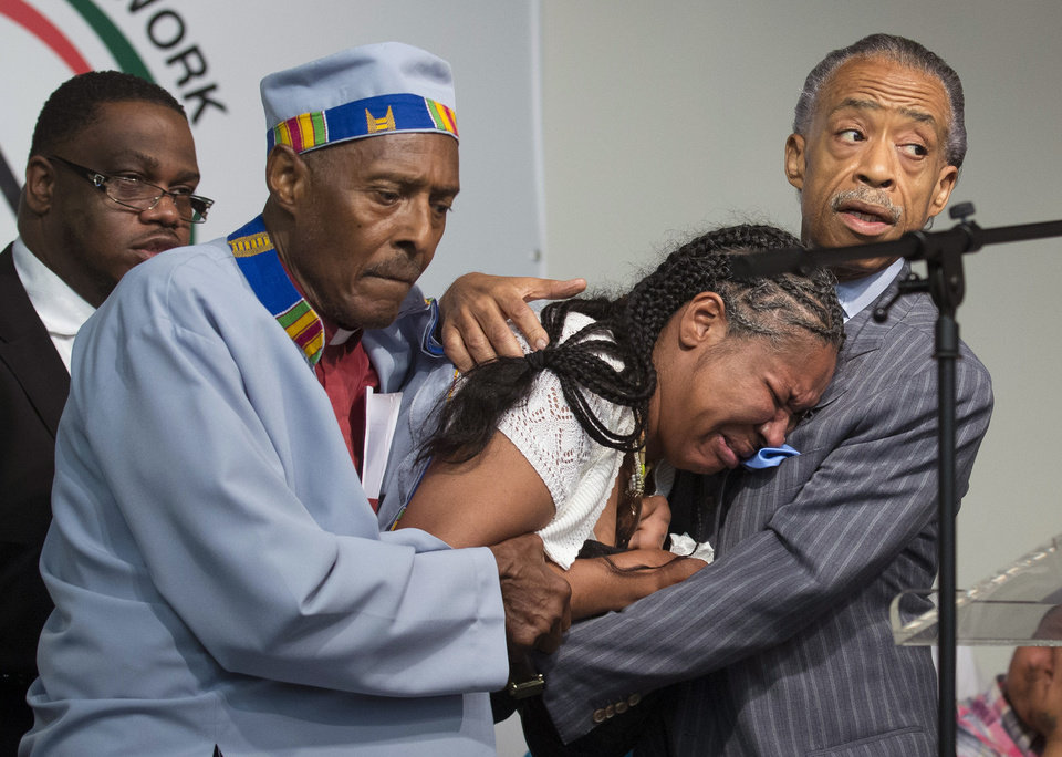 Photo - Esaw Garner, center, wife of Eric Garner, breaks down in the arms of Rev. Herbert Daughtry and Rev. Al Sharpton, right, during a rally at the National Action Network headquarters for Eric Garner, Saturday, July 19, 2014, in New York. Garner, 43, died Thursday, during an arrest in Staten Island, when a plain-clothes police officer placed him in what appeared be a chokehold while several others brought him to the ground and struggled to place him in handcuffs. (AP Photo/John Minchillo)