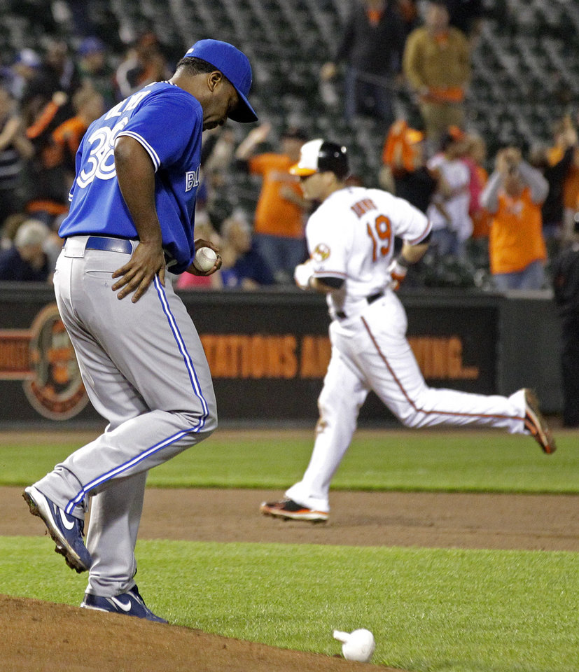 Photo -   Toronto Blue Jays relief pitcher Darren Oliver walks on the mound as Baltimore Orioles' Chris Davis rounds the bases after hitting a two-run home run in the eighth inning of a baseball game in Baltimore, Thursday, April 26, 2012. Baltimore won 5-2. (AP Photo/Patrick Semansky)