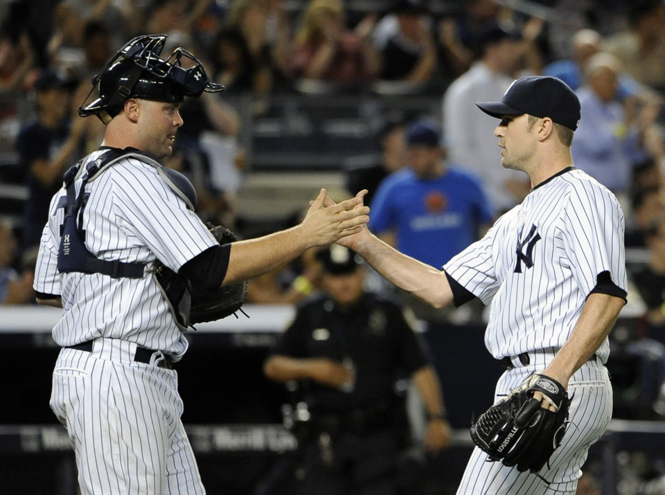 Photo - New York Yankees catcher Brian McCann congratulates relief pitcher David Robertson after the Yankees defeated the Cincinnati Reds 4-3 in an interleague baseball game at Yankee Stadium on Friday, July 18, 2014, in New York. (AP Photo/Kathy Kmonicek)