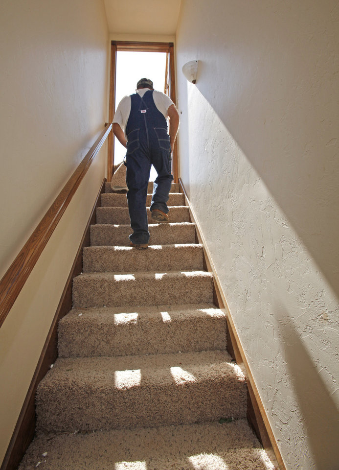 Daylight streams down the stairs that once led to the second floor of David and Tiffany Swanson's two-story home as David's father Ted walks up them on Thursday, May 26, 2011, in Blanchard, Okla.  The second floor is now in the front yard. Photo by Steve Sisney, The Oklahoman