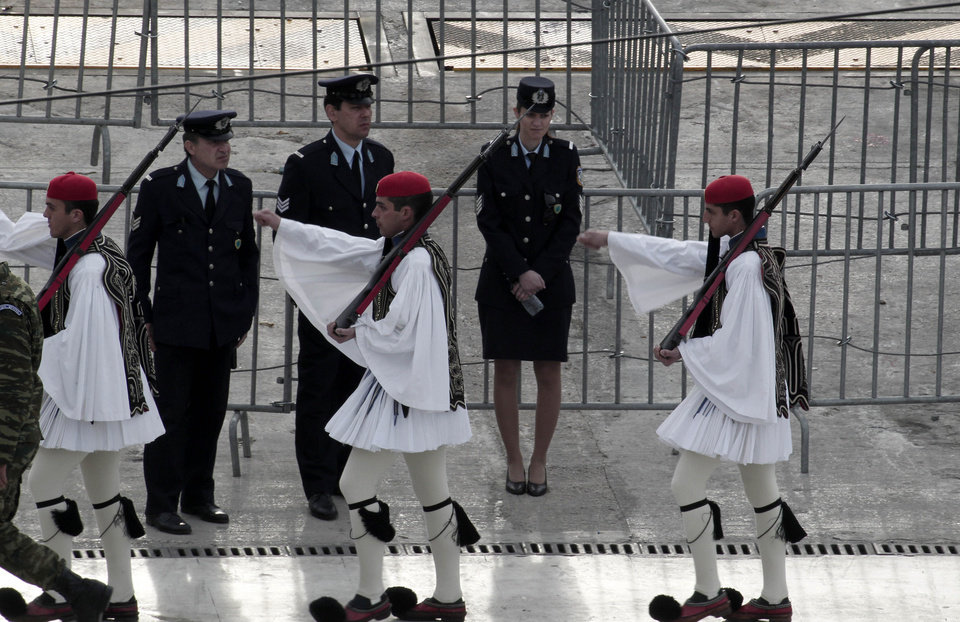 Greek Presidential guards walk past a double security metallic barriers and police officers after the changing of the guards at the Unknown Soldier Monument in front of the Parliament in Athens on Sunday March 25, 2012. Greek authorities have launched a massive security operation across central Athens for a military parade in the capital to mark the country's independence day, for fear that anti-austerity protests could disrupt the march. Thousands of police have been mobilized, while traffic on all major routes leading to the parade area has been blocked off. For the first time, the public will be banned from a large part of the route, including the area in front of Parliament from where politicians and other officials will watch the march. (AP Photo/Dimitri Messinis)