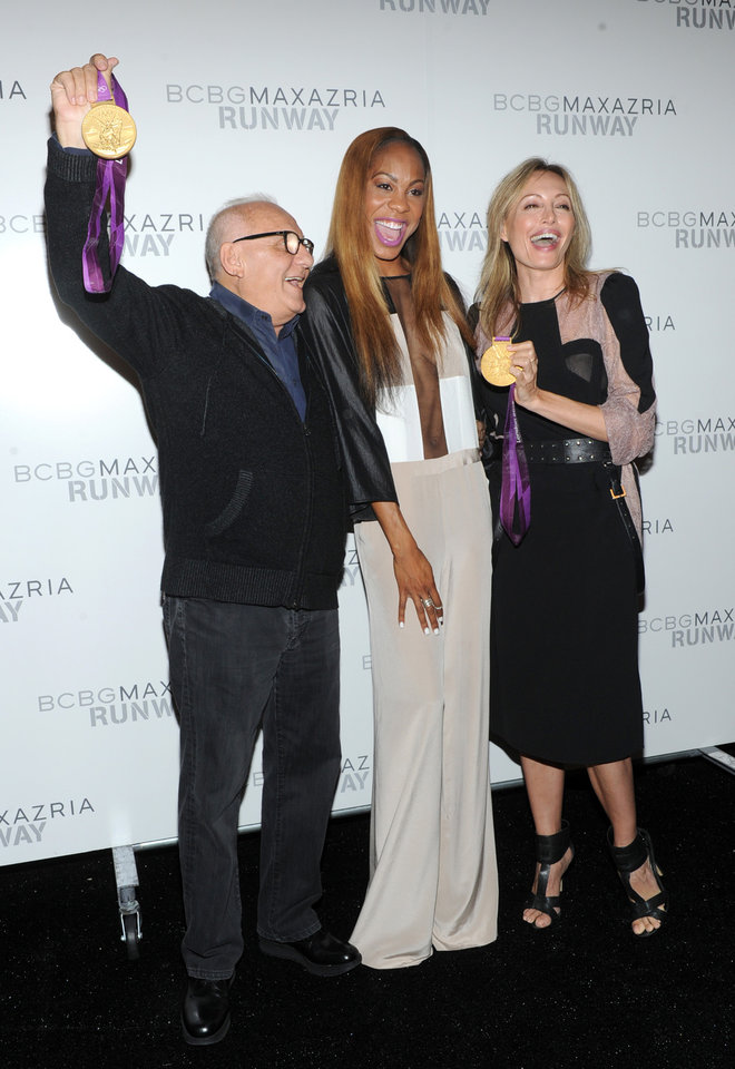 Photo -   Olympic gold medalist Sanya Richards-Ross, center, shows her medals to designers Max, left, and Lubov Azria before the BCBG MAX AZRIA Spring 2013 collection is shown at Fashion Week in New York, Thursday, Sept. 6, 2012. (Photo by Diane Bondareff/Invision/AP Images)