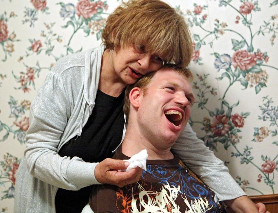 COMMUNITY CARE: James Bowman gets a hug from one of his caregivers, Sherry Spangler, at a home he shares with roommates in Oklahoma City on Wednesday, August 25, 2010. Photo by John Clanton, The Oklahoman ORG XMIT: KOD
