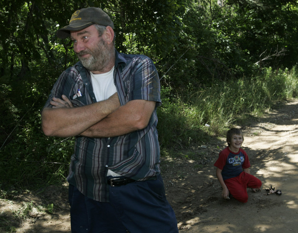 Photo - Ross Padgett, , left, talks with a reporter as his son, Devon, age 7, plays on the side of the road near a memorial or Skyla Whitaker and Taylor Paschal-Placker, Wednesday, June 11, 2008. The girls were found murdered Sunday night. (AP Photo)