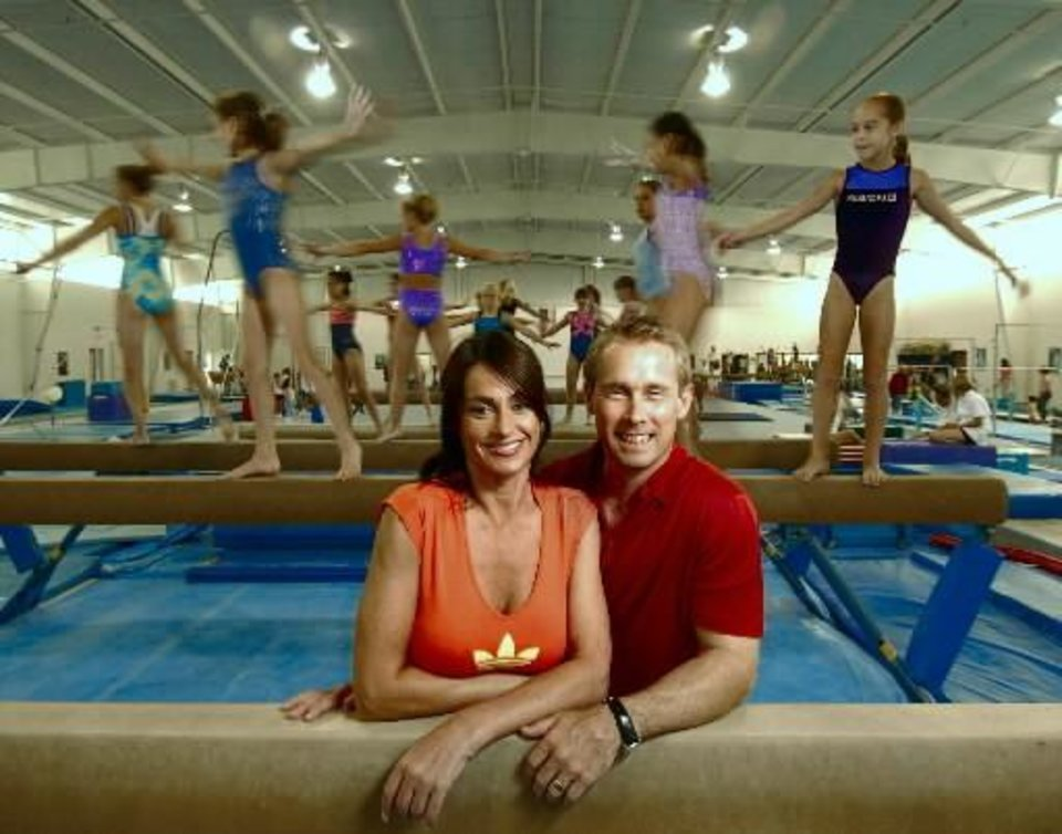 Photo - Bart Conner and wife  Nadia  Comaneci pose for a photograph inside the Bart Conner Gymnastic Academy in Norman, Thurday, August 5, 2004. Staff photo by Bryan Terry