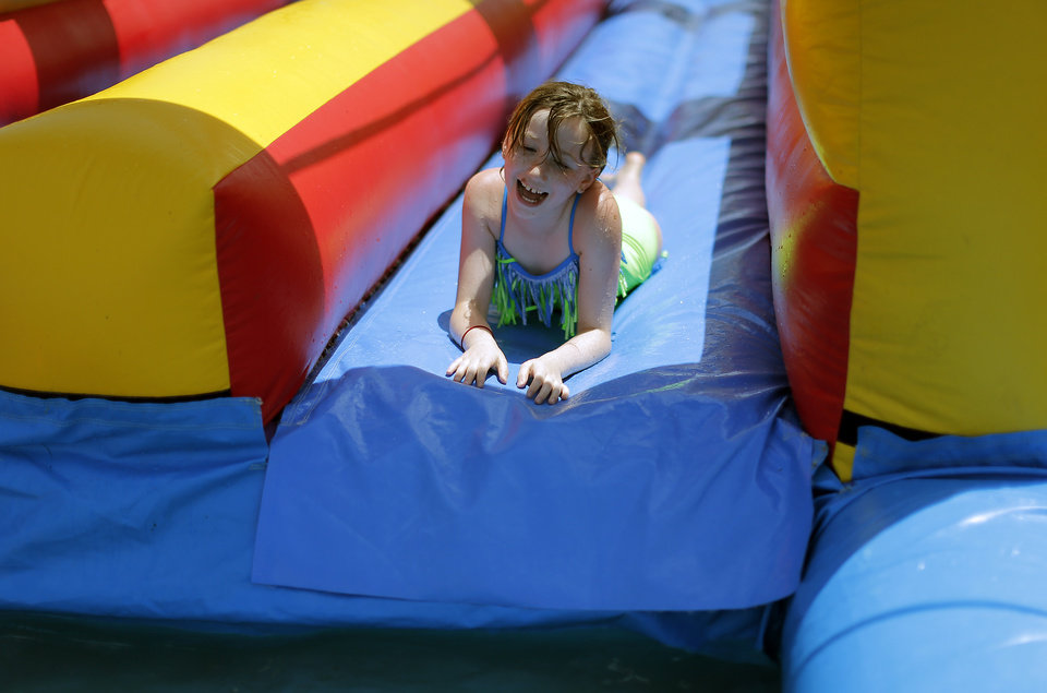 Photo - Lexi Dubord slide on an inflatable water slide during Kamp Kanakuk at Faith Bible Church in Edmond. Photo by Sarah Phipps, The Oklahoman  SARAH PHIPPS