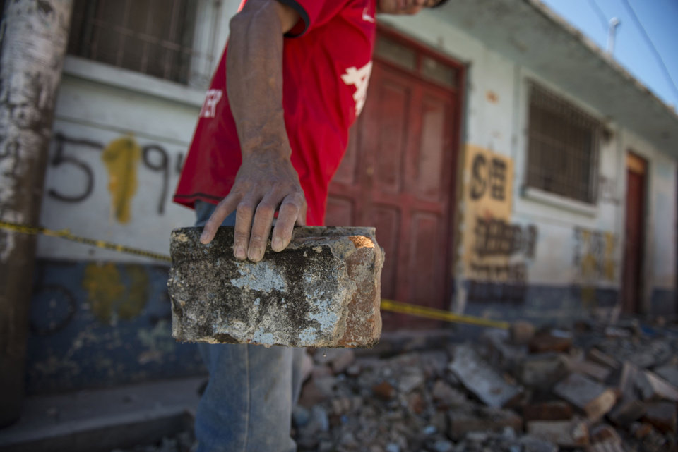 Photo - A man removes bricks from the front of his home that was damaged during an earthquake in San Pedro, Guatemala, Monday, July 7, 2014. A magnitude-6.9 earthquake on the Pacific Coast jolted a wide area of southern Mexico and Central America Monday. (AP Photo/Oliver de Ros)