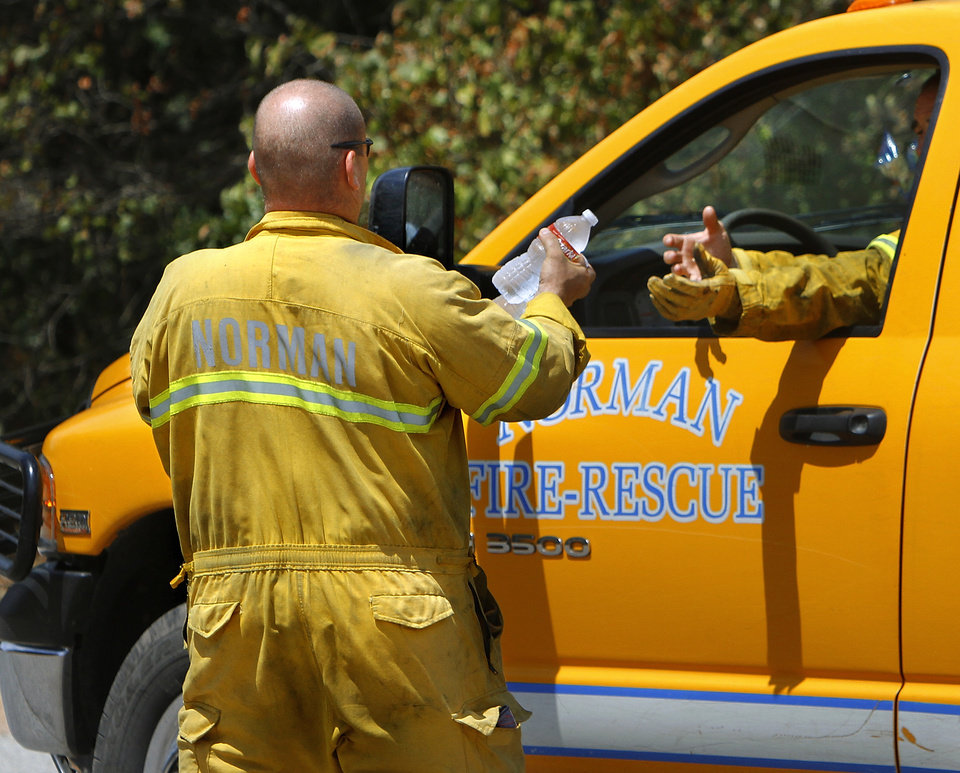 Photo - A Norman firefighter gives bottles of cold water to fellow firefighters inside a firetruck as they prepare to venture into a heavily wooded area north of SH 9 near Lake Thunderbird to extinguish flare-ups. Norman firefighters continued to extinguish small grass fires on Monday, Aug. 6, 2012, three days after a massive wildfire scorched more than 10 square miles of  dry land, destroying dozens of homes and structures as it swept across  rural sections  of southeast Cleveland County.    Photo by Jim Beckel, The Oklahoman.