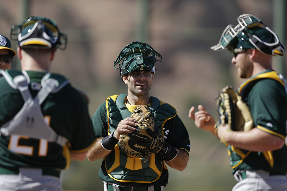 Photo - Oakland Athletics invitee catcher Dusty Brown, center, listens to Athletics catchers Stephen Vogt, left, and Chris Gimenez, right, during spring training baseball practice Saturday, Feb. 15, 2014, in Scottsdale, Ariz.  (AP Photo/Gregory Bull)