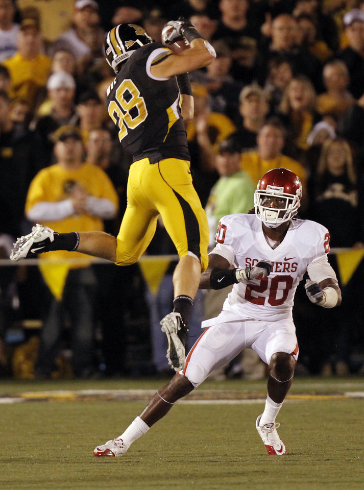 Photo - Missouri's T.J. Moe (28) makes a reception in front of Oklahoma's Quinton Carter (20)  during the second half of the college football game between the University of Oklahoma Sooners (OU) and the University of Missouri Tigers (MU) on Saturday, Oct. 23, 2010, in Columbia, Mo. Oklahoma lost the game 36-27. Photo by Chris Landsberger, The Oklahoman