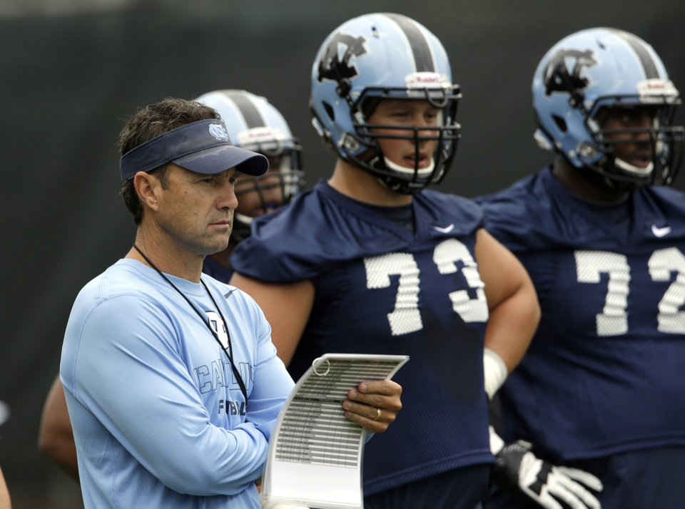 Photo - In this photo taken Friday, Aug. 1, 2014,  North Carolina coach Larry Fedora watches his team during an NCAA football practice in Chapel Hill, N.C. Brad Henson (73) and Kiaro Holts (72) look on at right. (AP Photo/Gerry Broome)