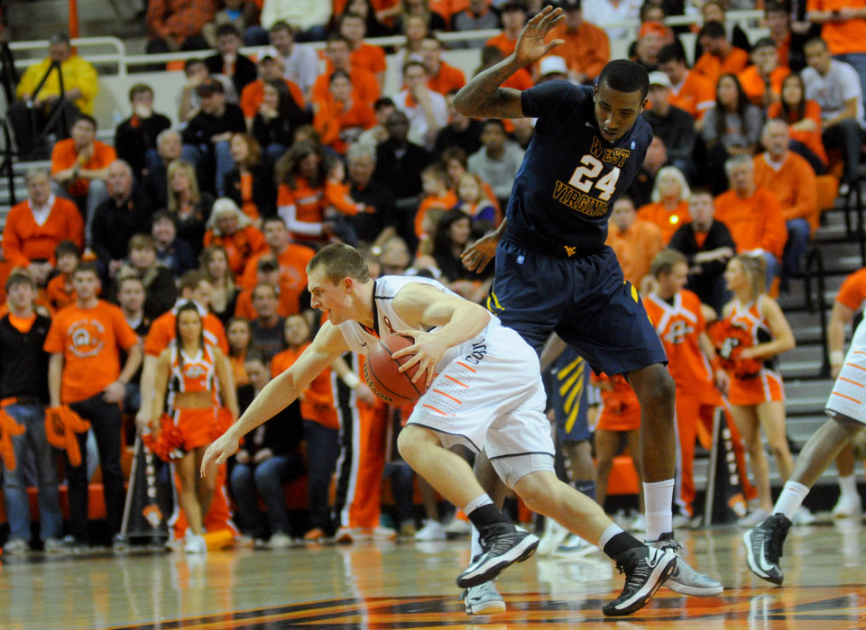 Photo - Oklahoma State guard Phil Forte dribbles around West Virginia defender Aaric Murray during an NCAA college basketball game in Stillwater, Okla., Saturday, Jan. 26, 2013. (AP Photo/Tulsa World, KT King)  ONLINE OUT; TV OUT; TULSA OUT