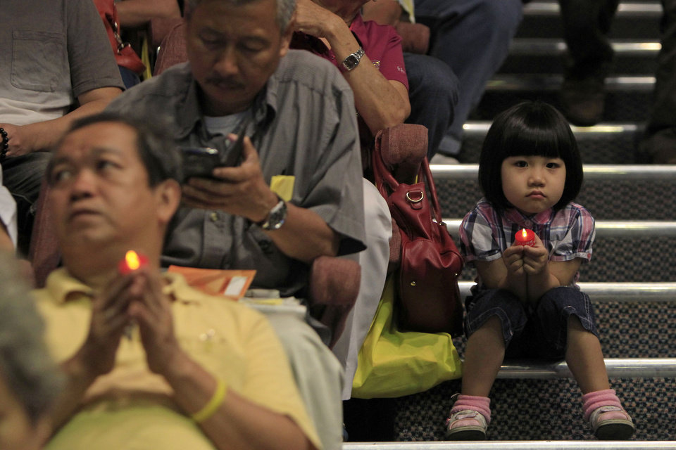 Photo - A girl holding a LED candle as she joins a mass prayer for the missing Malaysia Airlines Flight MH370, in Kuala Lumpur, Malaysia, Sunday, April 6, 2014. The head of the multinational search for the missing Malaysia airlines jet said that electronic pulses reportedly picked up by a Chinese ship are an encouraging sign but stresses they are not yet verified. (AP Photo/Lai Seng Sin)
