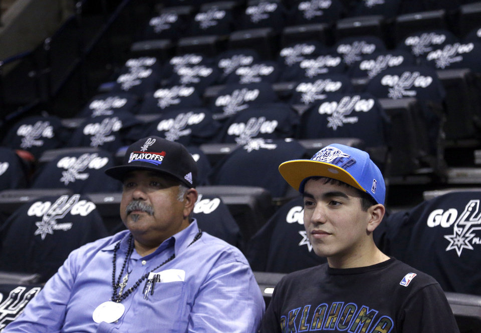 Photo - Spurs Fan Johnny Rodriquez and his son Thunder fan John Paul watch the Thunder warm up before Game 1 of the Western Conference Finals in the NBA playoffs between the Oklahoma City Thunder and the San Antonio Spurs at the AT&T Center in San Antonio, Monday, May 19, 2014. Photo by Sarah Phipps, The Oklahoman