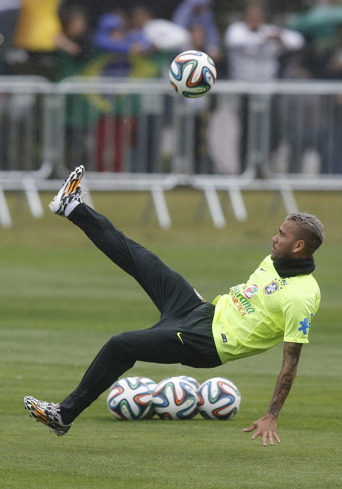Photo - Brazil's Daniel Alves kicks the ball during practice at the Granja Comary training center in Teresopolis, Brazil, Friday, July 11, 2014. Brazil will face the Netherlands in the World Cup third-place match Saturday. (AP Photo/Leo Correa)
