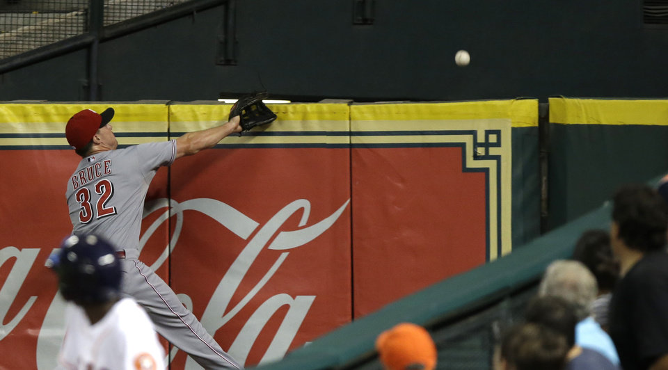 Photo - A ball boy and fans turn to watch Cincinnati Reds right fielder Jay Bruce's (32) futile attempt to catch a home run by Houston Astros' Brandon Barnes in the third inning of a baseball game Wednesday, Sept. 18, 2013, in Houston. (AP Photo/Pat Sullivan)