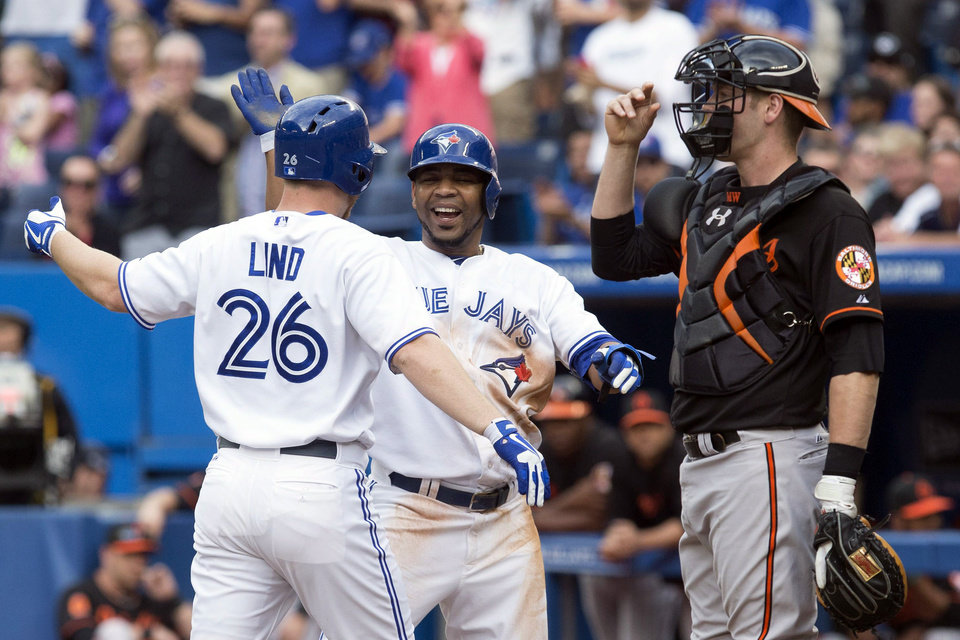 Photo - Toronto Blue Jays' Adam Lind, left, celebrates with Edwin Encarnacion after hitting a two-run homer off Baltimore Orioles starting pitcher Jason Hammel as Orioles catcher Matt Wieters looks on during the first inning of a baseball game in Toronto on Friday, June 21, 2013. (AP Photo/The Canadian Press, Chris Young)