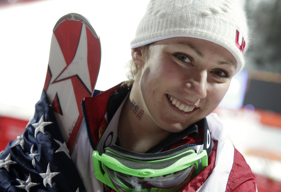 Photo - Women's slalom gold medal winner Mikaela Shiffrin of the United States wears an American flag after a flower ceremony at the Sochi 2014 Winter Olympics, Friday, Feb. 21, 2014, in Krasnaya Polyana, Russia.(AP Photo/Gero Breloer)
