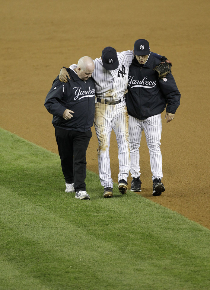 Photo -   Trainer Steve Donohue, left, and New York Yankees manager Joe Girardi, right, help Derek Jeter off the field after he injured himself during Game 1 of the American League championship series against the Detroit Tigers Sunday, Oct. 14, 2012, in New York. (AP Photo/Kathy Willens)