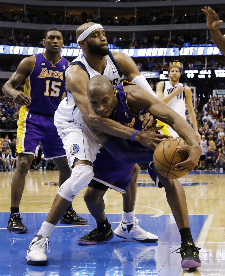 Photo - Dallas Mavericks' Vince Carter, center, fouls Los Angeles Lakers' Kobe Bryant as the two chase down a loose ball late in the second half of an NBA basketball game, Sunday, Feb. 24, 2013, in Dallas. The Lakers won 103-99. (AP Photo/Tony Gutierrez)