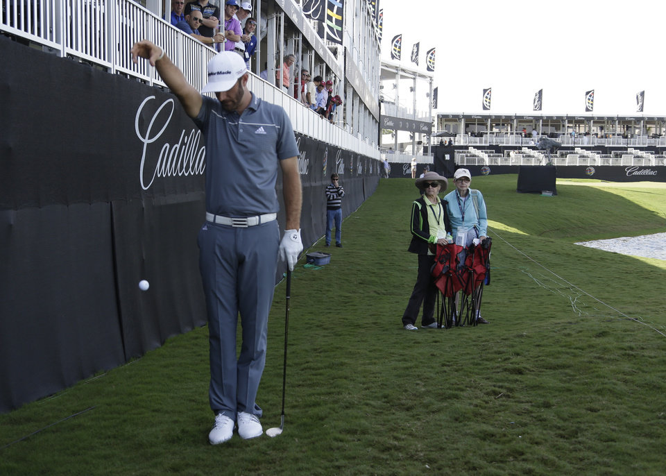 Photo - Dustin Johnson takes a drop on the ninth hole rough during the first round of the Cadillac Championship golf tournament Friday, March 7, 2014, in Doral, Fla.  A severe thunderstorm delayed  first round play on Thursday. (AP Photo/Lynne Sladky)