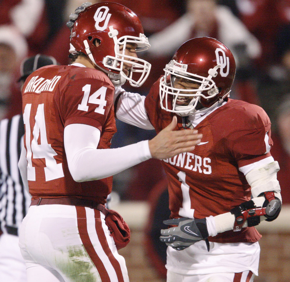 Photo - OU's Sam Bradford and Manuel Johnson celebrate after a touchdown during the college football game between the University of Oklahoma Sooners and Texas Tech University at Gaylord Family -- Oklahoma Memorial Stadium in Norman, Okla., Saturday, Nov. 22, 2008. BY BRYAN TERRY, THE OKLAHOMAN