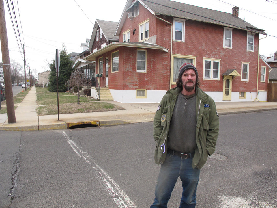 Photo - Taylor Rambo stands in front of his home in Burlington City, N.J. on Wednesday, March 19, 2014. If flooding were a real concern, he says he would not have built a bar in his basement. Yet he pays about $2,700 each year for flood insurance that he is required to have as part of his mortgage, and the amount is likely to rise quickly.