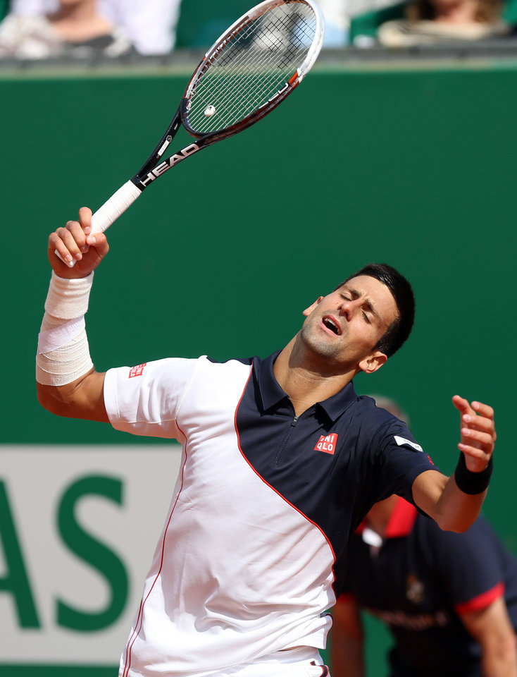 Photo - Novak Djokovic of Serbia reacts after losing a point against Roger Federer of Switzerland, during their semifinal match of the Monte Carlo Tennis Masters tournament,  in Monaco, Saturday, April, 19, 2014. Federer won 7-6, 6-2. (AP Photo/Claude Paris)