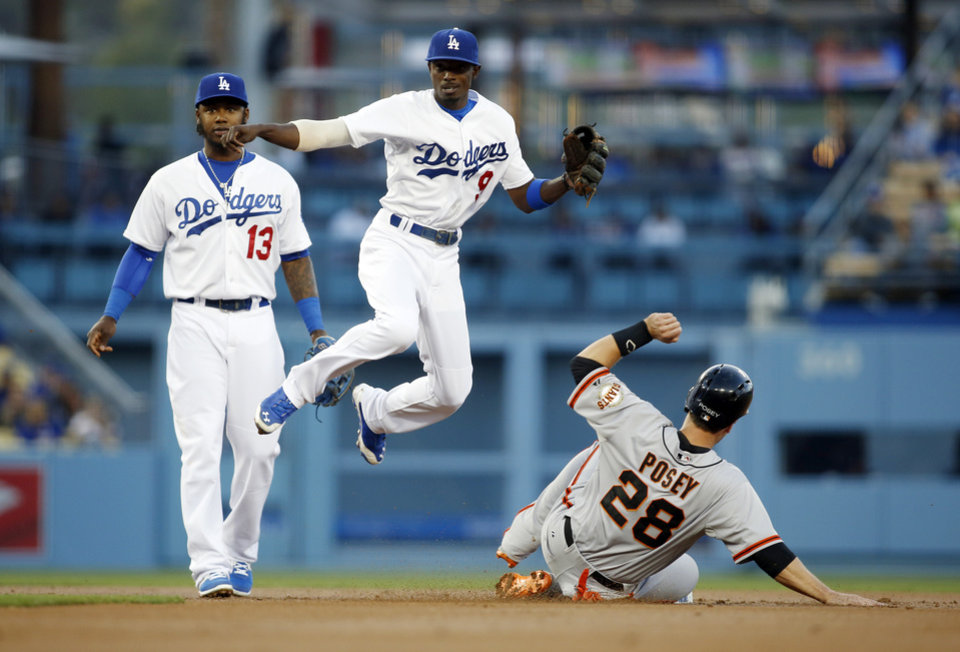 Photo - Los Angeles Dodgers second baseman Dee Gordon, center, forces out San Francisco Giants' Buster Posey, right, and throws out Michael Morse out at first base to complete the double play as shortstop Hanley Ramirez, left, stands near during the first inning of a baseball game, Friday, May 9, 2014, in Los Angeles. (AP Photo/Danny Moloshok)