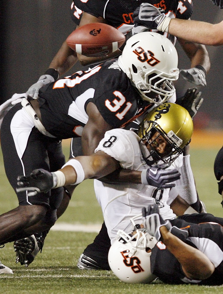 Photo - Colorado's Demetrius Sumler (8) fumbles the ball between OSU's Lucien Antoine (31) and Patrick Lavine (4), bottom, in the fourth quarter during the college football game between Oklahoma State University (OSU) and the University of Colorado (CU) at Boone Pickens Stadium in Stillwater, Okla., Thursday, Nov. 19, 2009. The Cowboys recovered the ball. OSU won, 31-28. Photo by Nate Billings, The Oklahoman