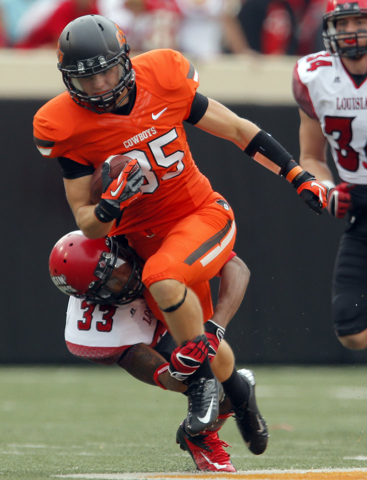 Photo - Oklahoma State's Blake Webb (85) runs after making a catch as Louisiana-Lafayette's Trevence Patt (33) tackles him during a college football game between Oklahoma State University (OSU) and the University of Louisiana-Lafayette (ULL) at Boone Pickens Stadium in Stillwater, Okla., Saturday, Sept. 15, 2012. Photo by Sarah Phipps, The Oklahoman