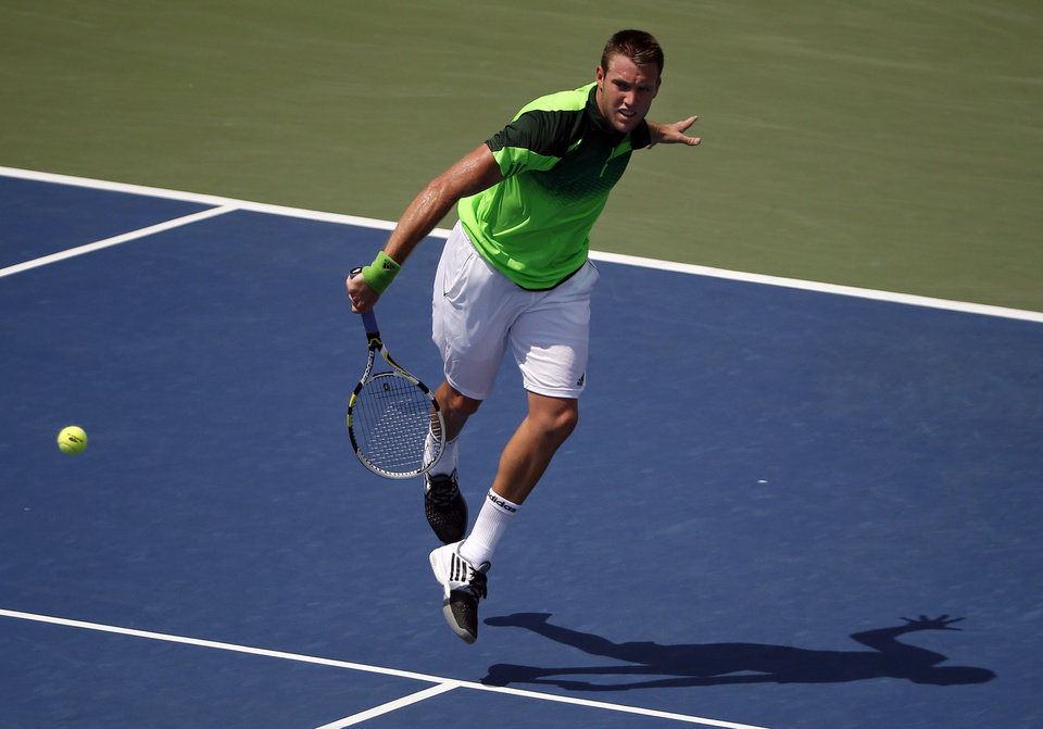 Photo - Jack Sock, of the United States, returns a shot against Pablo Andujar, of Spain, during the first round of the 2014 U.S. Open tennis tournament, Tuesday, Aug. 26, 2014, in New York. (AP Photo/Elise Amendola)