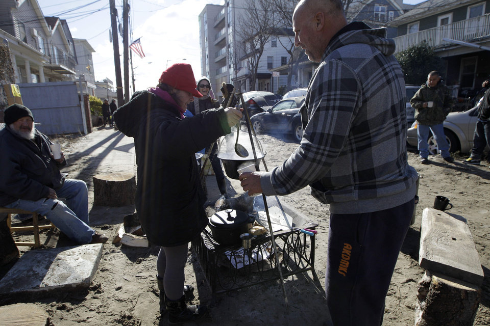 Photo -   Kiva Kahl pours hot tea for neighbor Buddy Sammis,right, after she prepared it on a wood-stoked fire and cooking setup she and her fiance created in the street in front of their house on Beach 91st Street in the Rockaways, Saturday, Nov. 3, 2012, in New York. More New Yorkers awoke Saturday to power being restored for the first time since Superstorm Sandy pummeled the region, but patience wore thin among those in the region who have been without power for most of the week. (AP Photo/Kathy Willens)