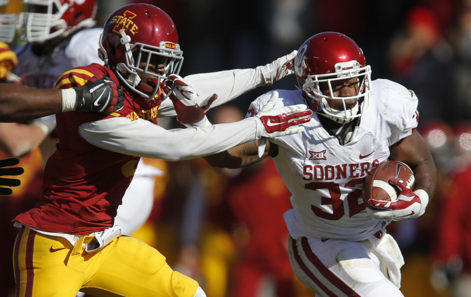 Photo - Oklahoma's Samaje Perine (32) fights off Iowa State's Kenneth Lynn (8) during a college football game between the University of Oklahoma Sooners (OU) and the Iowa State Cyclones (ISU) at Jack Trice Stadium in Ames, Iowa, Saturday, Nov. 1, 2014. Photo by Bryan Terry, The Oklahoman