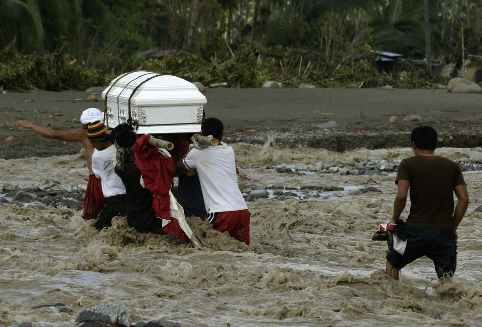 Relatives cross a river to bury their loved one, who died in a flash flood caused by Typhoon Bopha, Thursday, Dec. 6, 2012, in New Bataan township, Compostela Valley in the southern Philippines. The powerful typhoon that washed away emergency shelters, a military camp and possibly entire families in the southern Philippines has killed hundreds of people with nearly 400 missing, authorities said Thursday. (AP Photo/Bullit Marquez)